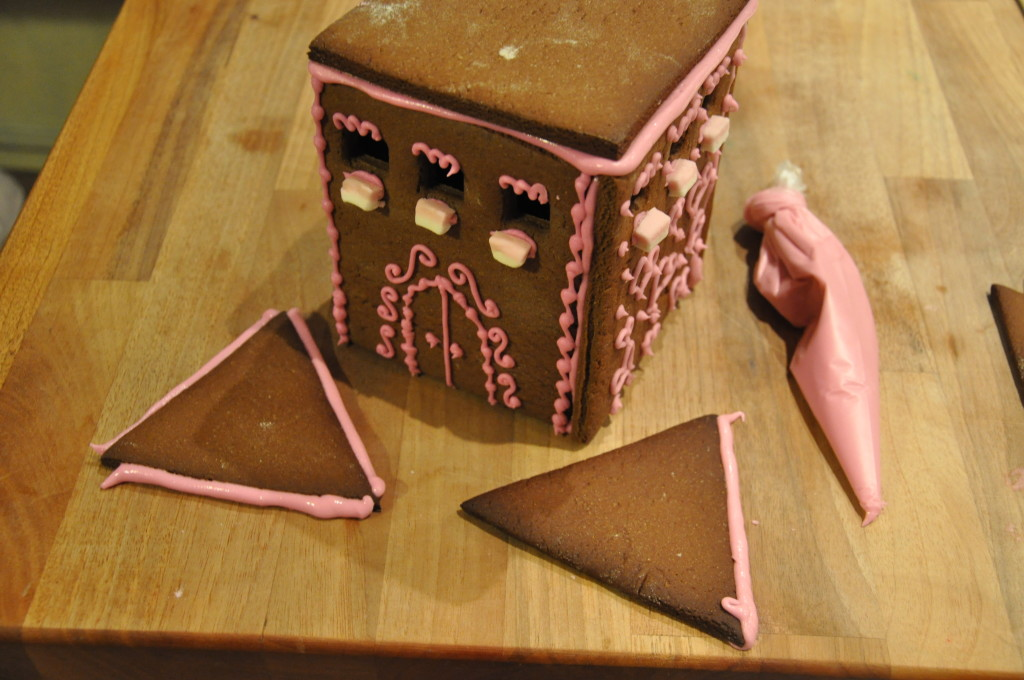 Using icing as a glue to add a roof to the gingerbread castle
