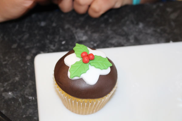 Putting The Icing Berries On Top Of The Cupcake