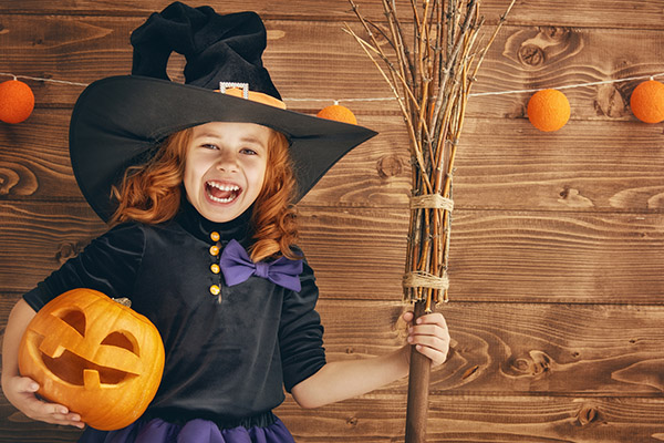 Cute little witch costume with a pumpkin.